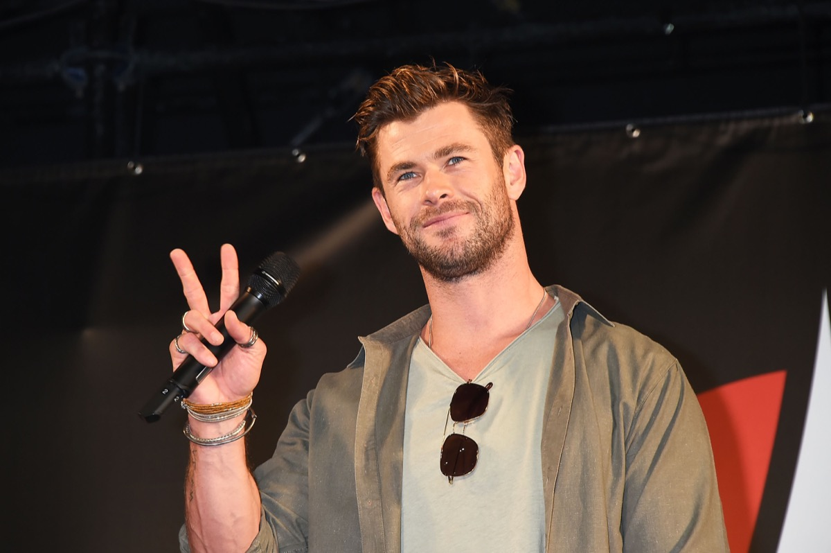 chris hemsworth giving peace sign on red carpet