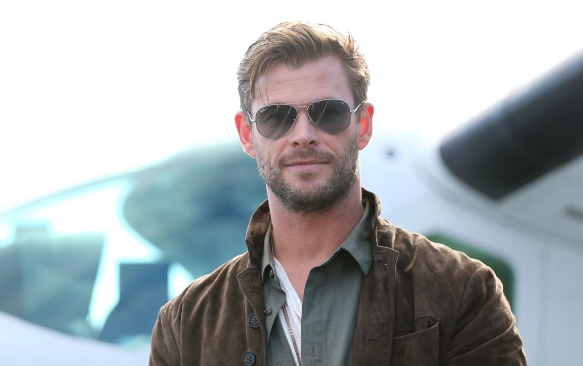 chris hemsworth in sunglasses standing outdoors
