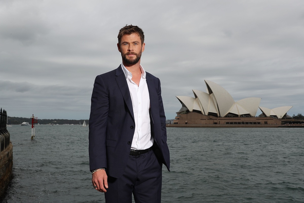 chris hemsworth standing in front of the Sydney Opera House