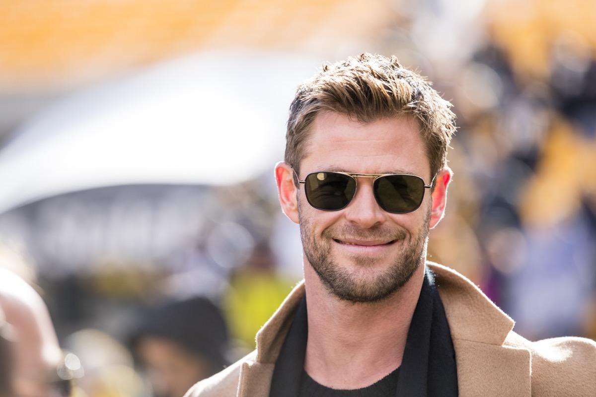 chris hemsworth smiling in a tan coat and sunglasses