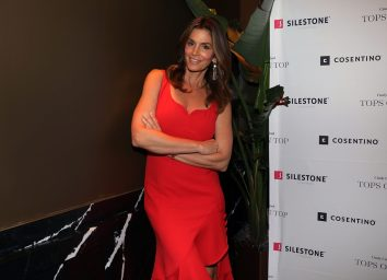 cindy crawford crossing her arms while wearing a red dress