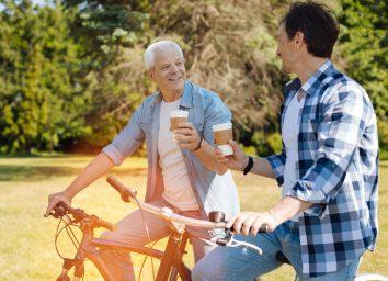 two men on bikes drinking coffee