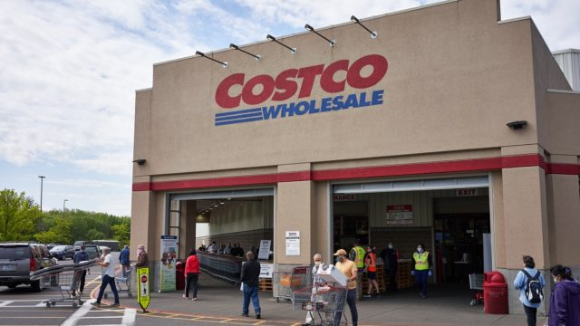 Masked shoppers outside a Costco store
