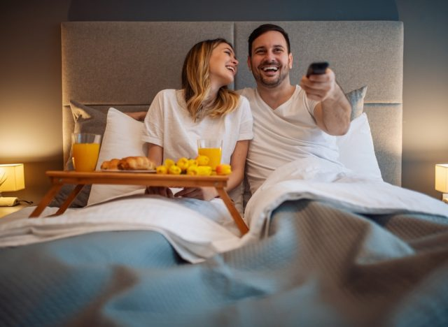 30-something couple eating breakfast in bed and watching tv
