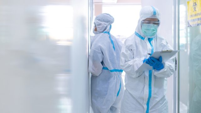 Two doctors in personal protective equipment or ppe including white suit, mask, face shield and gloves.