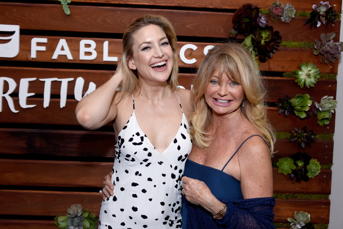 kate hudson and goldie hawn posing in front of fabletics step-and-repeat
