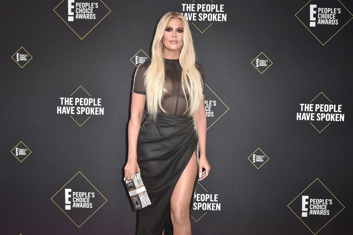 khloe kardashian on red carpet in sheer top and black skirt