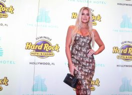 khloe kardashian standing in snakeskin print dress in front of hard rock step and repeat