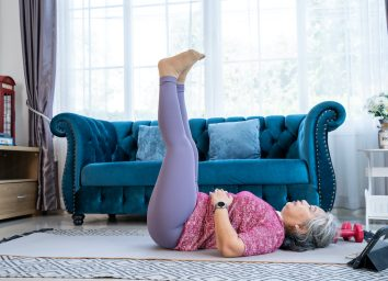 Healthy Senior woman lie on the floor and raise two leg up while doing exercise stretching legs with lying leg lift, workout fitness pose at home