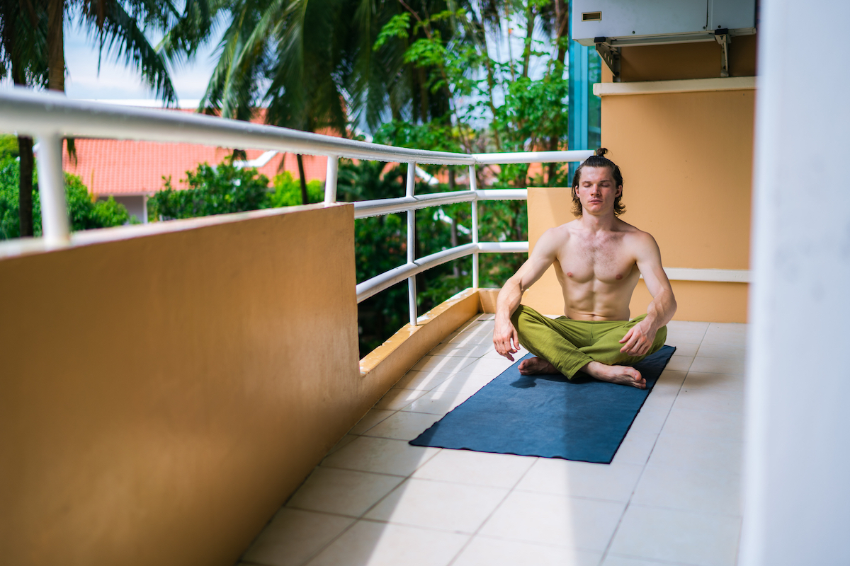 Handsome man practicing yoga on a balcony at home. Male yogi sitting on mat in meditation