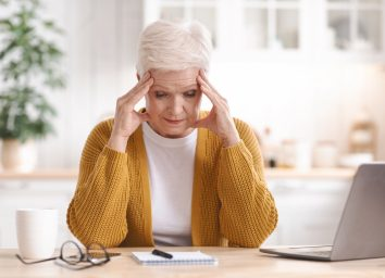 Senior lady taking notes, sitting in front of computer, touching her head