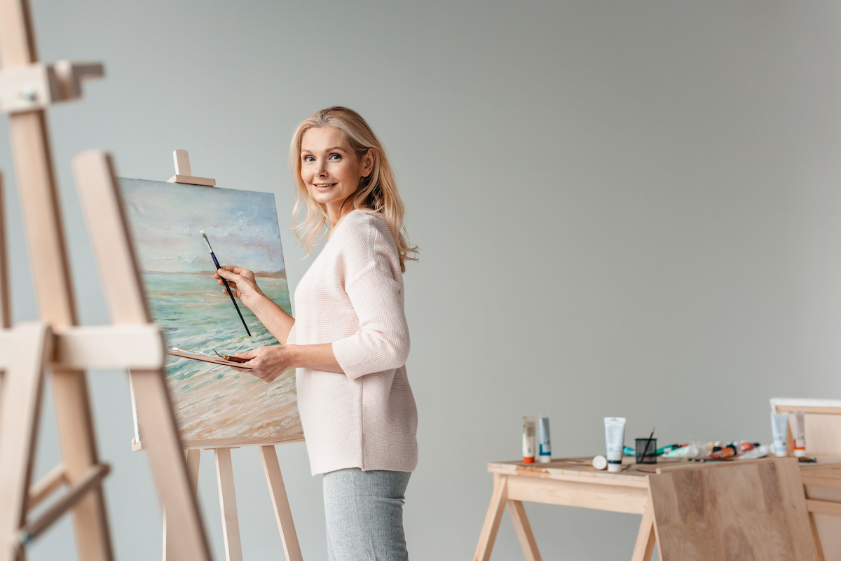 mature female artist smiling at camera while painting on easel in art studio