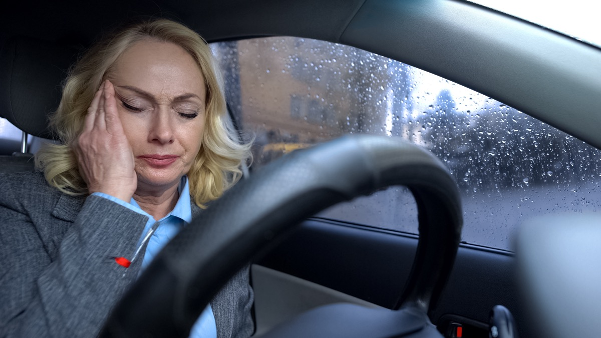 Mature business female sitting in a car on rainy day