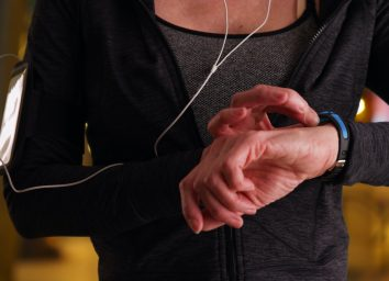 Close up of fit senior woman using activity tracker