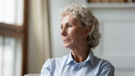 sad senior 70s grandmother look in distance thinking.