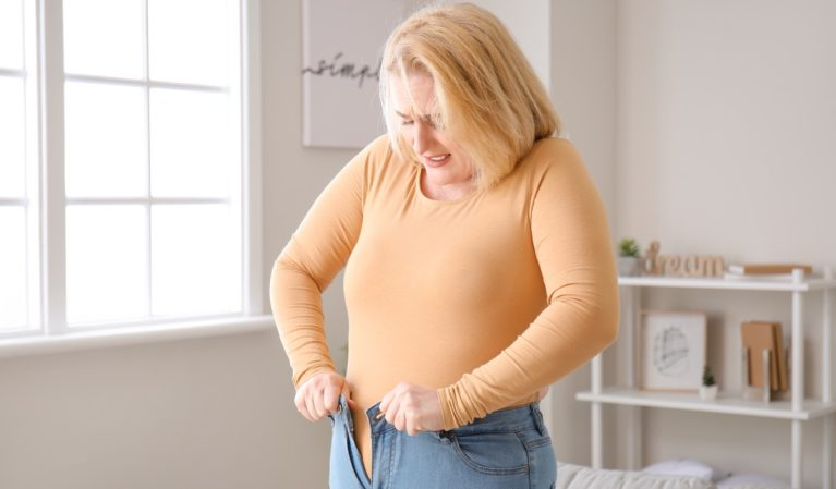 Overweight woman in tight clothes at home is trying to fit into tight jeans.