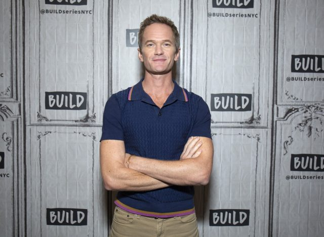 neil patrick harris with arms crossed wearing blue polo shirt in front of build studios step and repeat