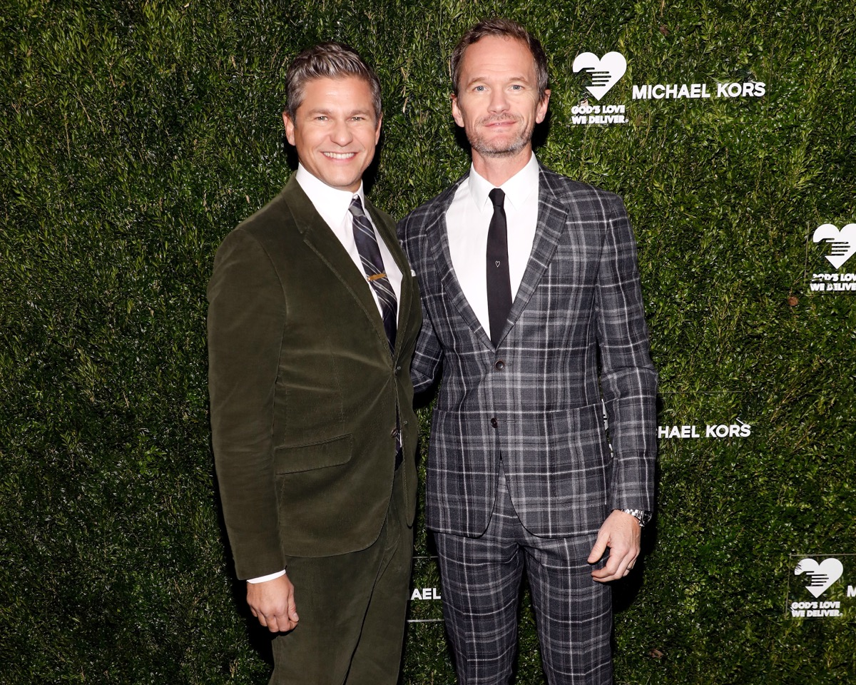 neil patrick harris in green velvet and blue plaid suits respectively in front of green living wall