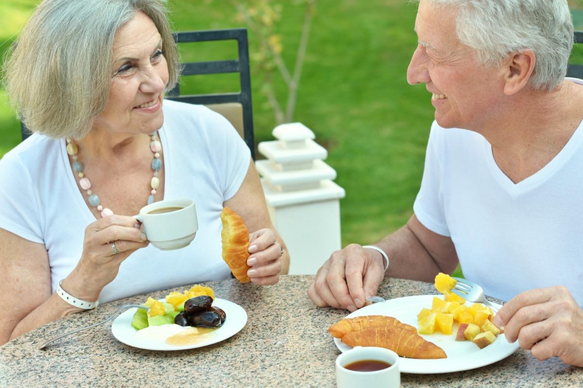 older couple eating croissants for breakfast