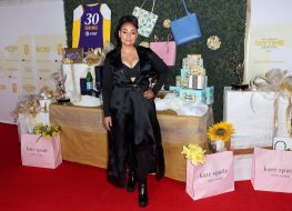 raven-symone in long black satin dress or cape in front of gifting suite and pink kate spade bags