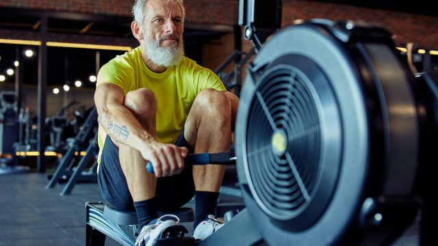 Sport and fitness after 50. Strong mature athletic man in sportswear exercising on rowing machine at gym