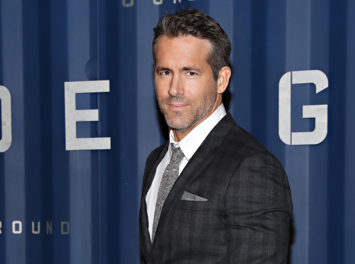 ryan reynolds wearing a black suit on the red carpet