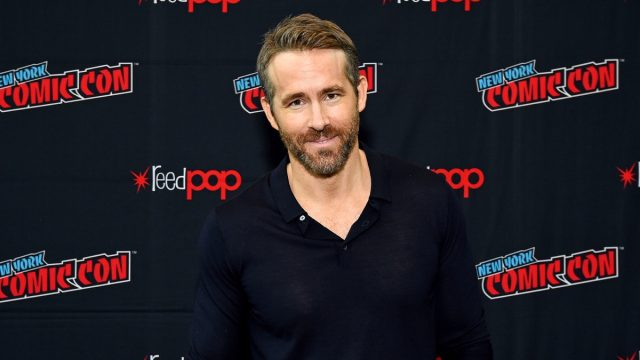 ryan reynolds in black unbuttoned henley in front of ny comic-con step and repeat