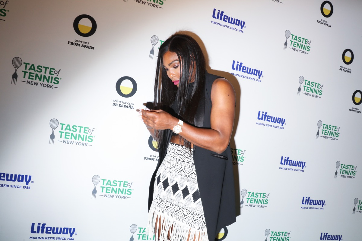 serena williams looking at her phone on the red carpet