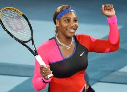 serena williams raising her fist on tennis court while holding racket
