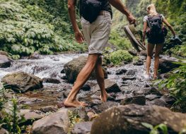 couple-hiking-barefoot-over-stream