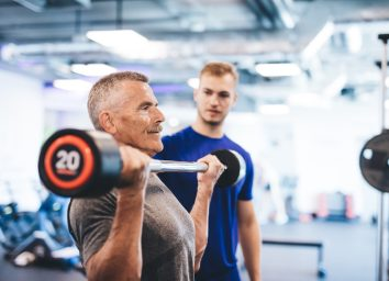 older man lifting weights at gym with spotter