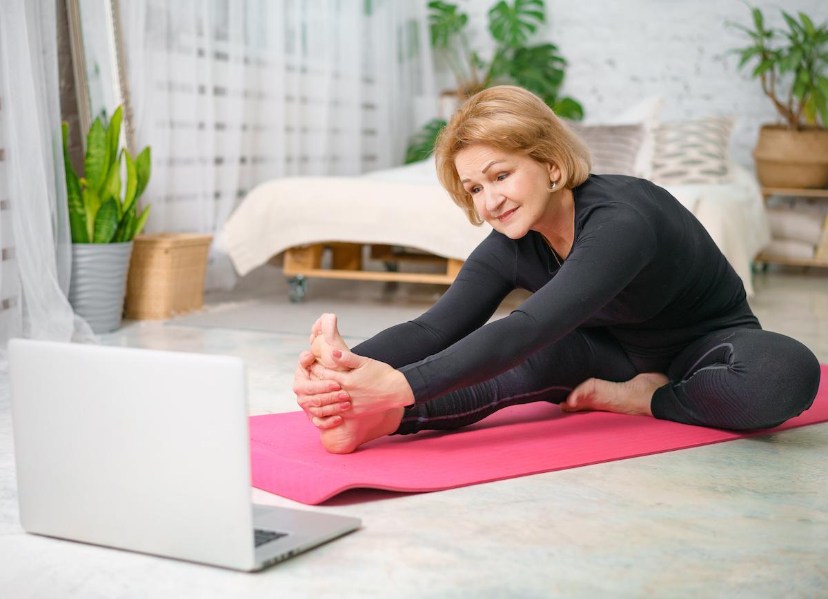older-woman-stretching-on-yoga-mat