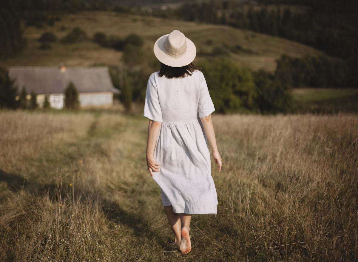 woman-in-white-dress-walking-barefoot-in-field
