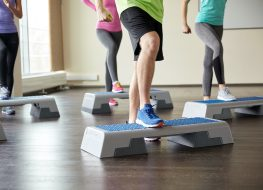 fitness, sport, aerobics and people concept - group of smiling people working out and flexing legs on step platforms in gym