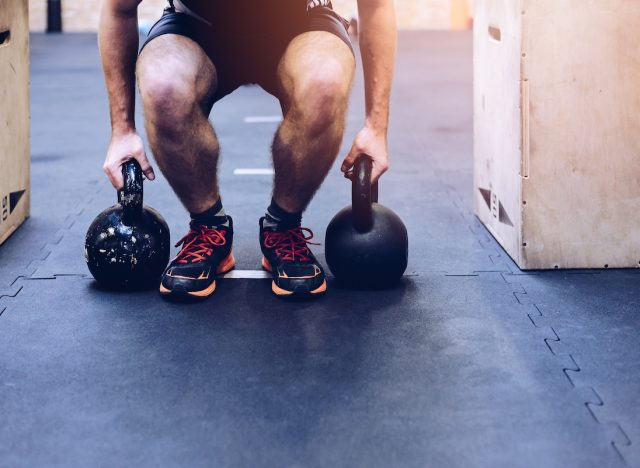 Man pulling kettlebells weights in the functional fitness gym. Kettle bell deadlift