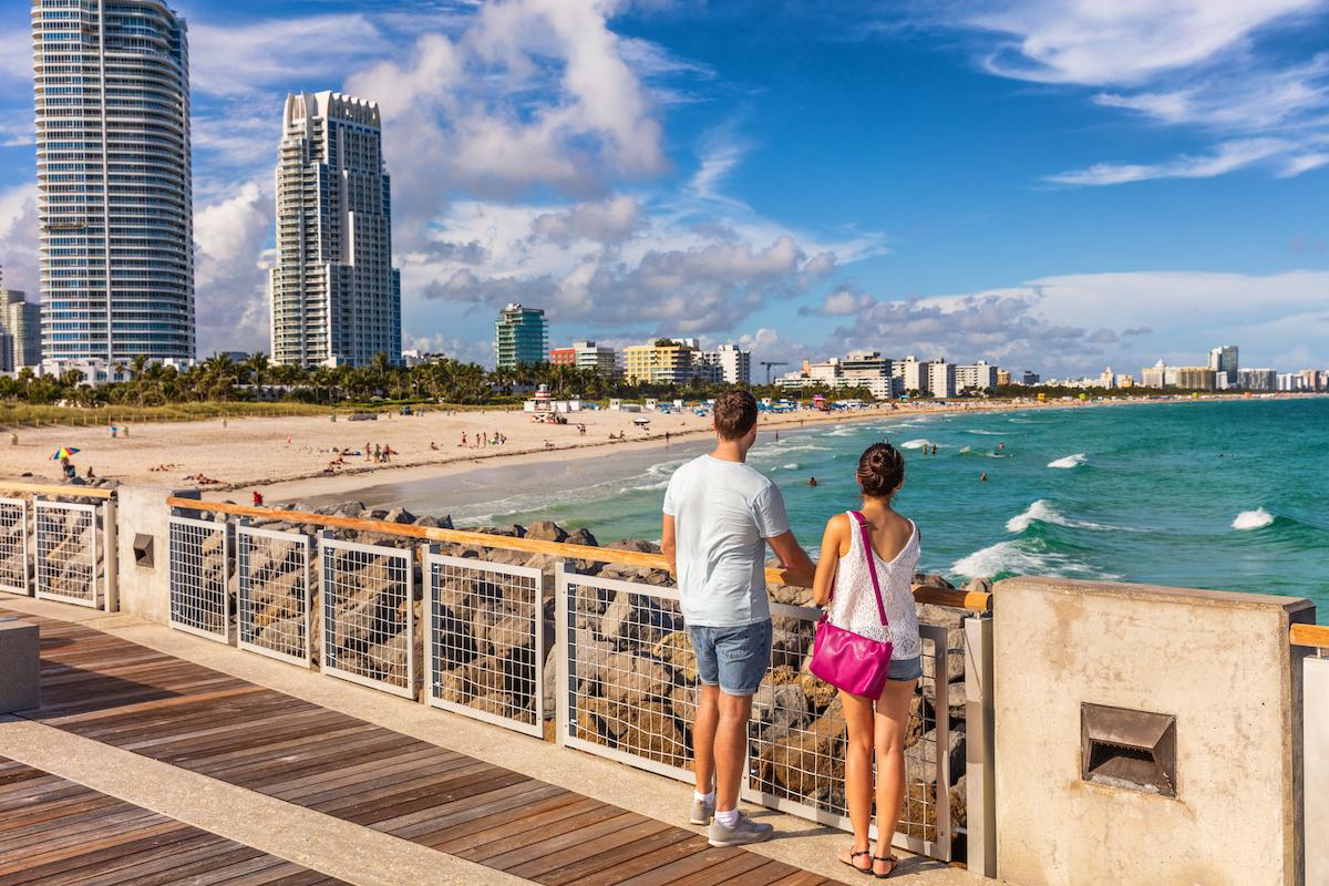 Miami beach tourists couple walking in South Beach, Miami, Florida. USA travel.