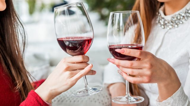 a woman in a red shirt and a woman in a white shirt toasting with glasses of wine