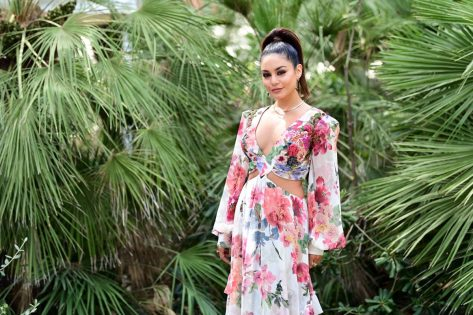 vanessa hudgens in long floral dress in front of greenery
