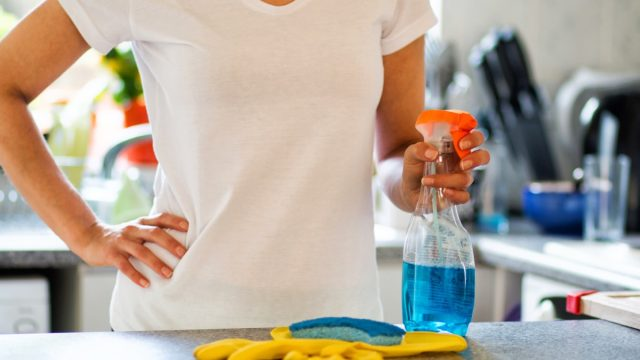 woman in white shirt holding cleaning supplies with gloves and sponge on counter in foreground