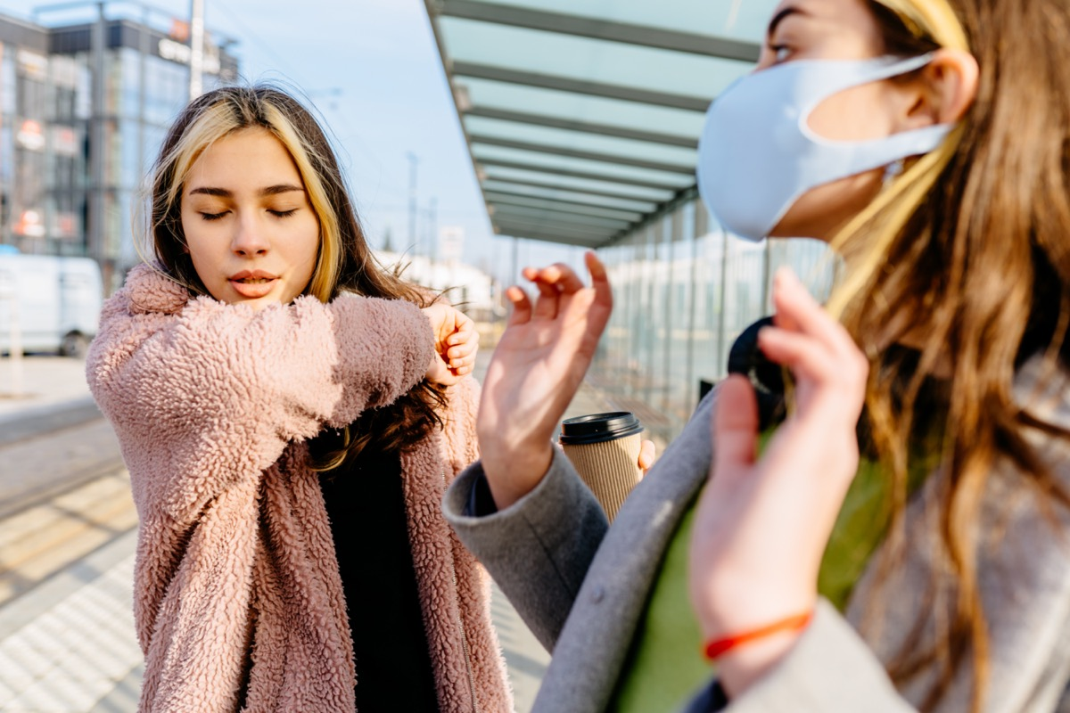 Young sick student teenager woman outside at bus stop is sneezing into the elbow by an allergy or cold. Scared woman in protective mask afraid cough woman outdoor