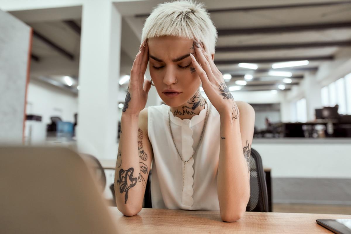 Utrujena mlada tetovirana poslovna ženska, ki sedi na svojem delovnem mestu v sodobni pisarni, zaprtih oči, se dotika glave in trpi zaradi glavobola