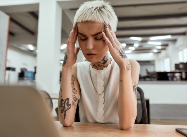 Exhausted young tattooed business woman keeping eyes closed, touching head and suffering from the headache while sitting at her working place in the modern office