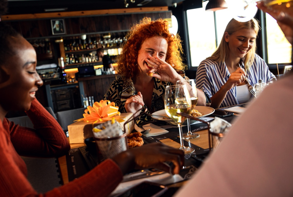 woman with red curly hair laughing with her two friends in a restaurant