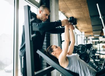 Beautiful woman helped by trainer in gym