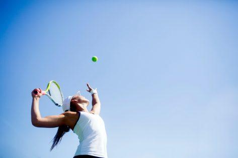 Beautiful female tennis player serving