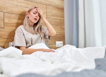 Woman being sick having flu sitting on bed alone at home, having high fever or temperature, touching forehead
