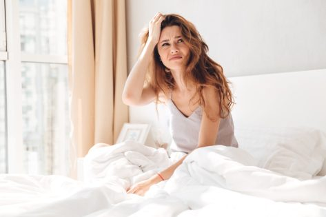 Annoyed brunette woman sitting in pajamas in bed and looking up