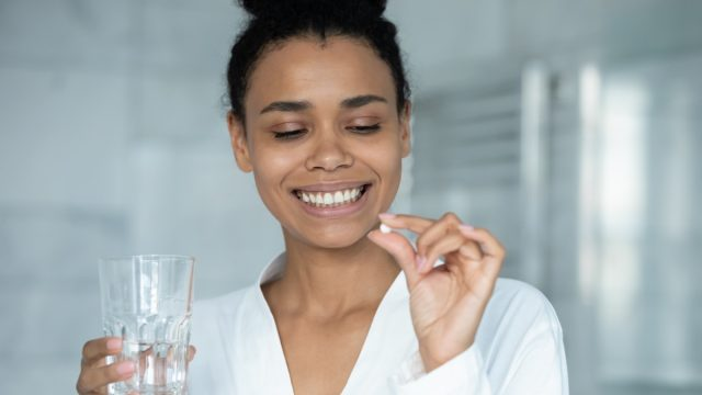 young woman in white shirt looking at pill and holding glass of water