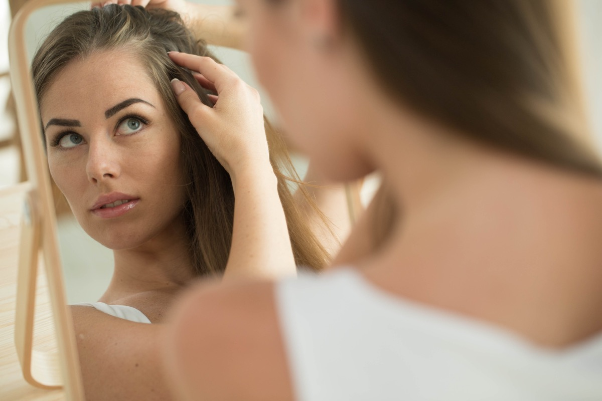 young woman looking at thinning hair in the mirror