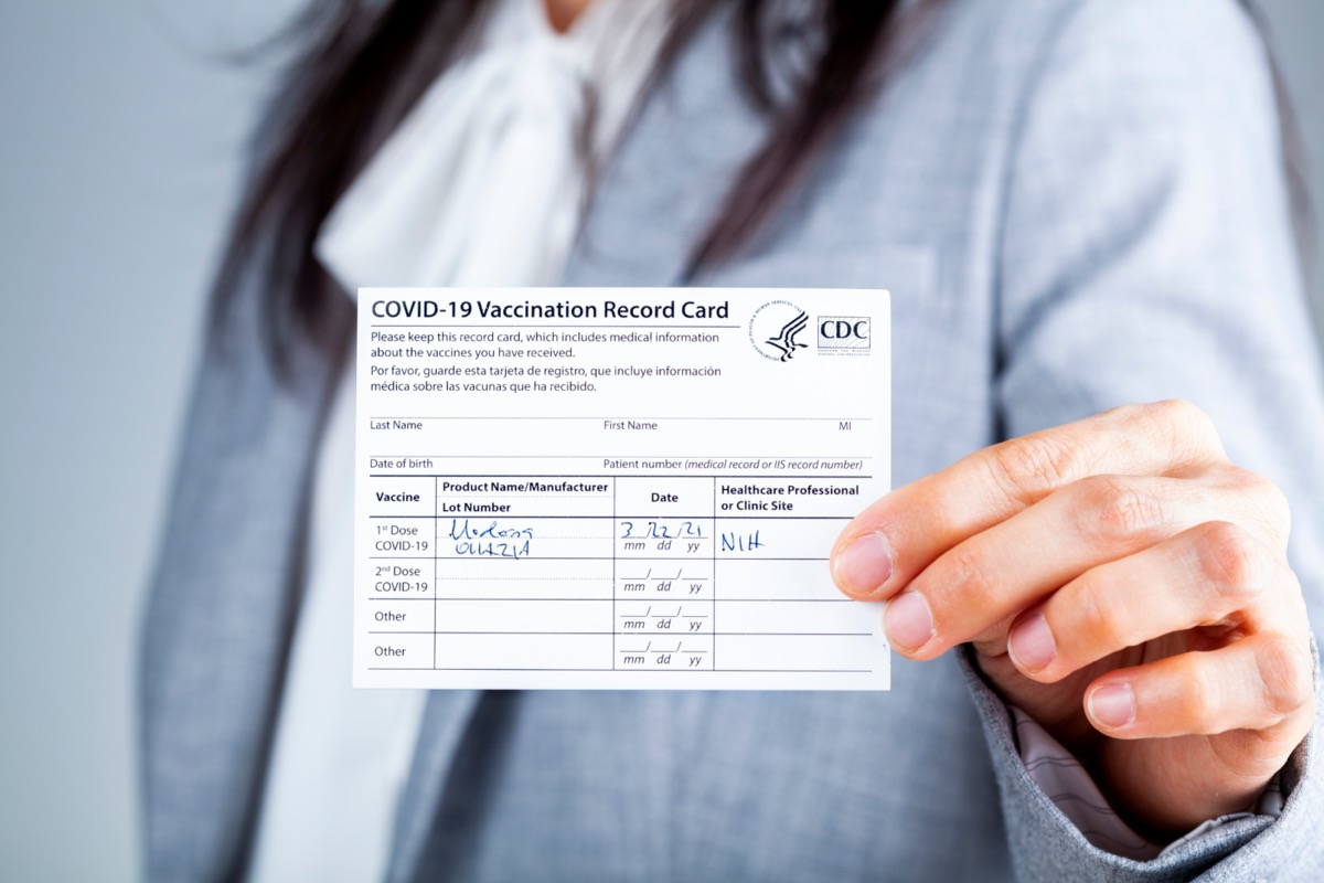 Woman is presenting COVID vaccination card.